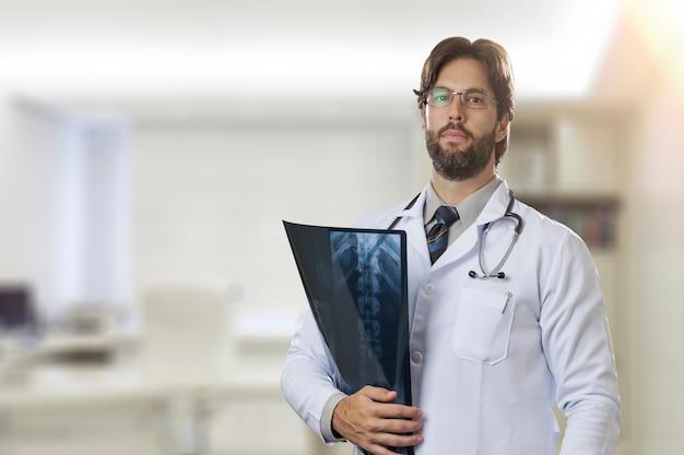 Medico maschio nel suo ufficio che esamina i raggi x