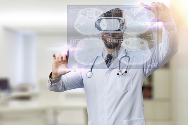 Medico maschio nel suo ufficio, utilizzando occhiali per realtà virtuale, guardando uno schermo virtuale
