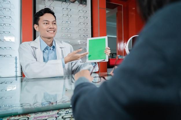 Un medico di sesso maschile sta mostrando una scheda di prova del colore che è una delle basi degli esami oculistici in una clinica oculistica