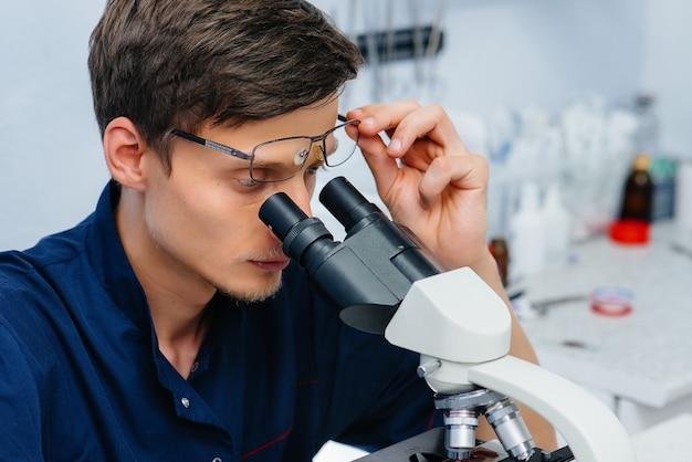 Un medico maschio in laboratorio studia virus e batteri