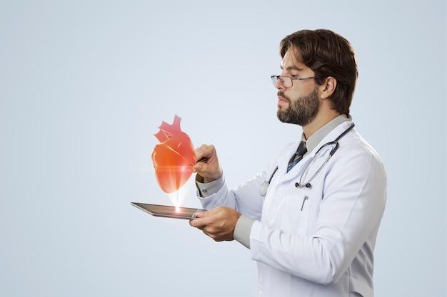 Medico maschio guardando un cuore virtuale che esce da un tablet su un muro grigio