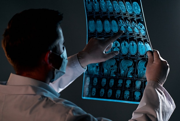 Un medico maschio in una maschera esamina una scansione a raggi x o mri di una scansione cerebrale di pazienti isolata sul nero.