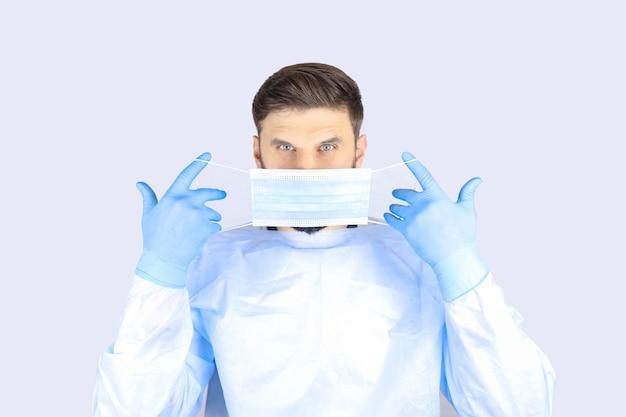 Medico maschio in un camice medico e guanti indossa una maschera protettiva