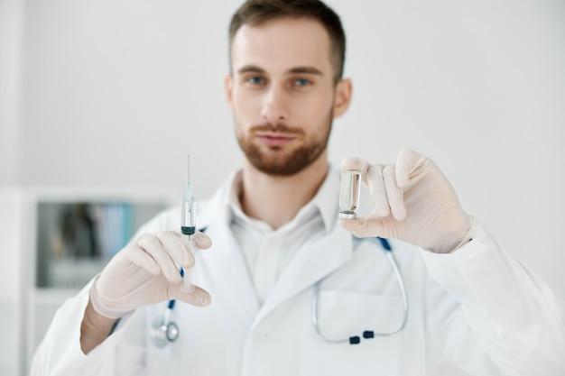 Medico maschio in un camice medico tiene una siringa in mano il liquido chimico del laboratorio di assistenza sanitaria del vaccino