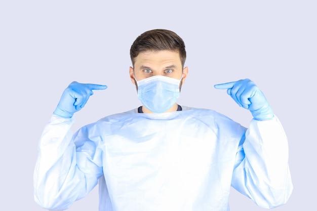 Medico maschio in un camice medico, maschera e guanti mostra i gesti delle dita