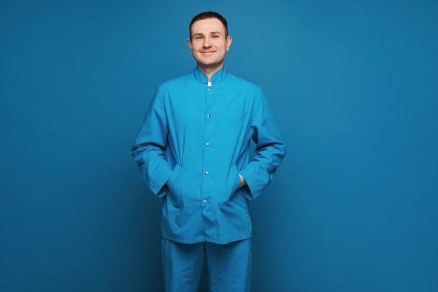 Un medico maschio in uniforme medica sorride e guarda la telecamera sullo sfondo blu giovane dottore ...
