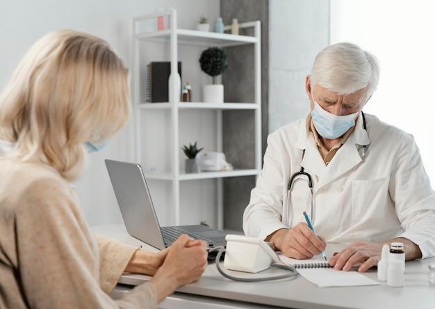 Medico maschio che prescrive pillole al paziente