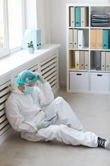 Medico maschio in abbigliamento protettivo seduto sul pavimento e utilizzando il suo telefono cellulare è stanco e riposa