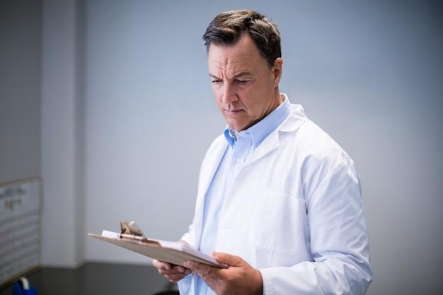 Medico maschio che legge rapporti in corridoio