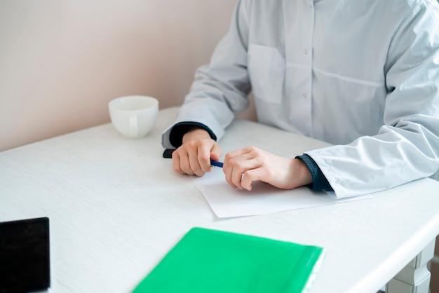 Medico maschio seduto al tavolo e ascolta il paziente in ospedale