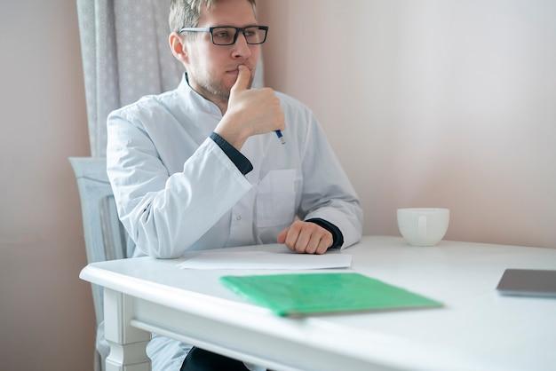 Un medico maschio seduto al tavolo e ascolta il paziente in ospedale