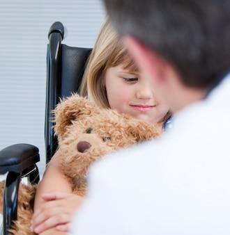 Medico maschio che parla con una bambina disabile