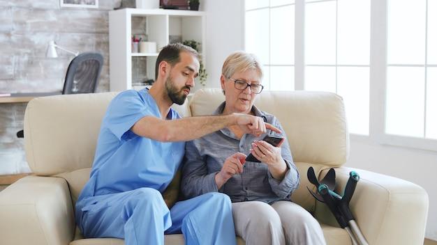 Medico maschio che insegna a una donna anziana come usare il telefono nella casa di cura