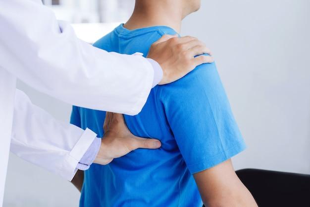 Terapista medico maschio che lavora esaminando il trattamento della schiena ferita. paziente con dolore alla schiena, trattamento, medico, massaggio per la sindrome dell'ufficio di sollievo dal dolore alla schiena.