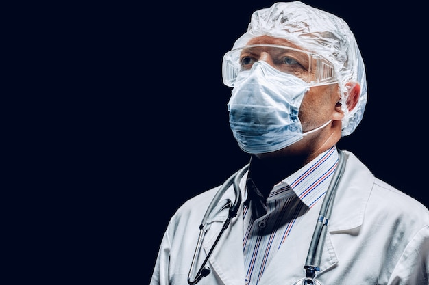 Medico maschio che indossa maschera protettiva e occhiali di protezione. sfondo scuro. avvicinamento.