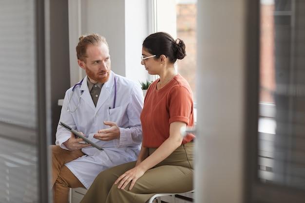 Medico maschio in camice bianco a parlare con il suo paziente mentre sono seduti nel corridoio dell'ospedale