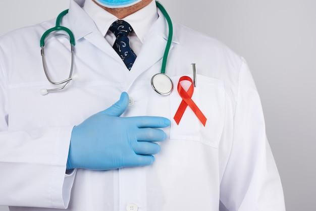 Dottore maschio in camice bianco e cravatta è in piedi, un nastro di seta rossa è appeso sul petto