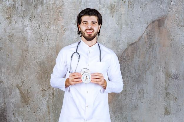 Medico maschio con uno stetoscopio che tiene una sveglia.