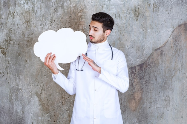 Medico maschio con lo stetoscopio che tiene una scheda informativa a forma di nuvola vuota e sembra premuroso.