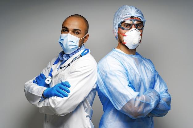 Medici maschi in uniforme medica che indossano maschere in piedi su sfondo grigio