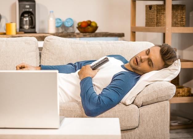 Vita domestica e rilassamento maschii su sofa at home