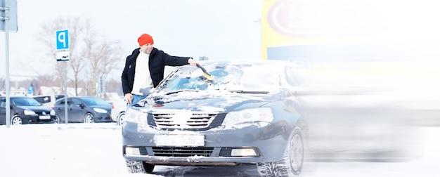 Un conducente di sesso maschile è in piedi davanti a un'auto. il proprietario pulisce l'auto dalla neve in inverno. auto dopo una nevicata.