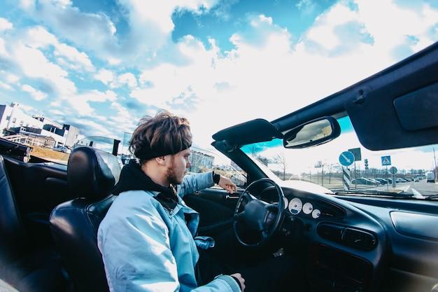 Autista maschio guida in una decappottabile per la città Foto Premium