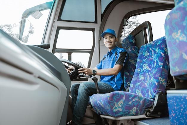 Un autista maschio in uniforme e cappello sorride alla telecamera mentre è seduto sull'autobus