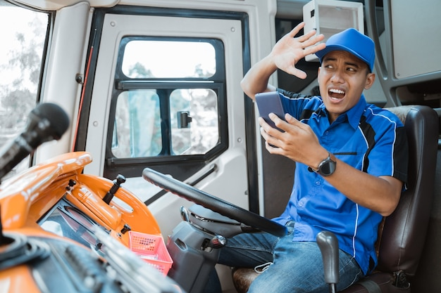 Un autista in uniforme guarda il suo cellulare mentre guida con noncuranza con un'espressione che si schianta all'interno dell'autobus