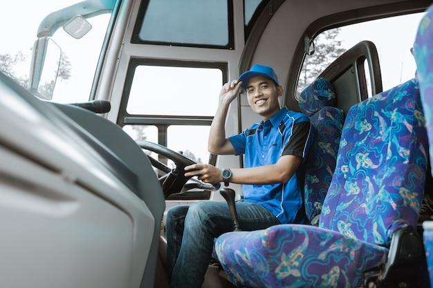 Un autista maschio in uniforme sorride alla telecamera mentre si siede e tiene un cappello sull'autobus