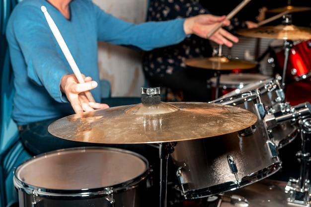 Il batterista maschio tiene i piatti con entrambe le mani e il batterista delle bacchette