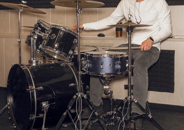 Il batterista maschio tiene in mano i piatti con entrambe le mani e il batterista delle bacchette