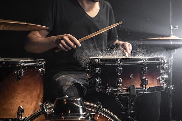 Un batterista maschio suona bacchette su un rullante con spruzzi d'acqua in una stanza buia.