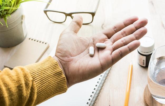 Maschio che mangia medicina, pillola sul lavoro nello stile di vita sano di mattina