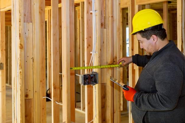 Il controllo maschio dell'ispettore del tecnico dell'elettricista controlla il pc della compressa della tenuta dell'elettricista del sistema elettrico