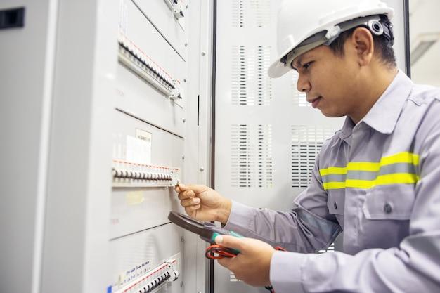 Un elettricista maschio lavora in un quadro elettrico scatola di giunzione dei terminali
