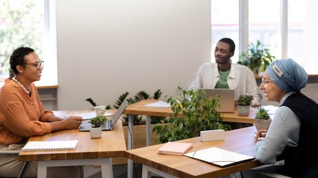 Impiegato maschio che conversa con i suoi nuovi colleghi al lavoro d'ufficio