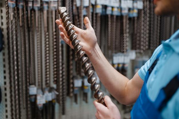 Dipendente maschio in uniforme scegliendo trapano per calcestruzzo nel negozio di utensili. scelta di attrezzature professionali in ferramenta, supermercato di strumenti