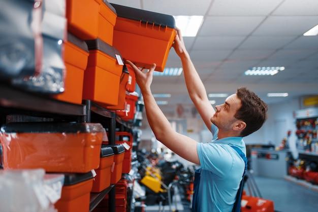 Dipendente maschio in uniforme scegliendo la cassetta degli attrezzi nel negozio di utensili. scelta di attrezzature professionali in ferramenta, supermercato di strumenti