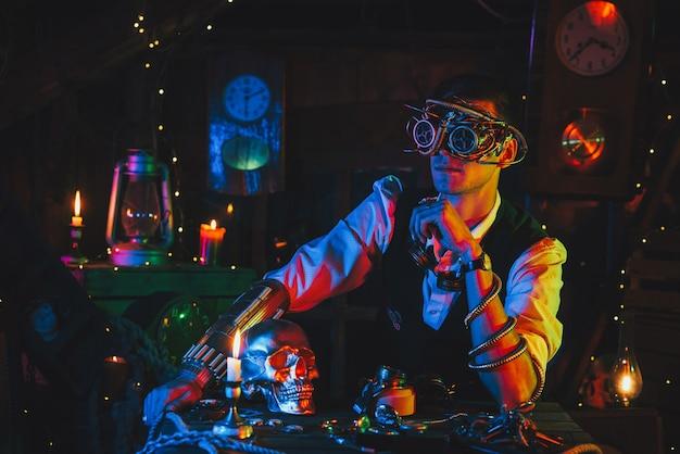 Ingegnere maschio con occhiali cyberpunk e un abito steampunk in un'officina con una luce al neon