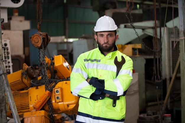 Ingegnere maschio in piedi con fiducioso contro l'ambiente della macchina in fabbrica
