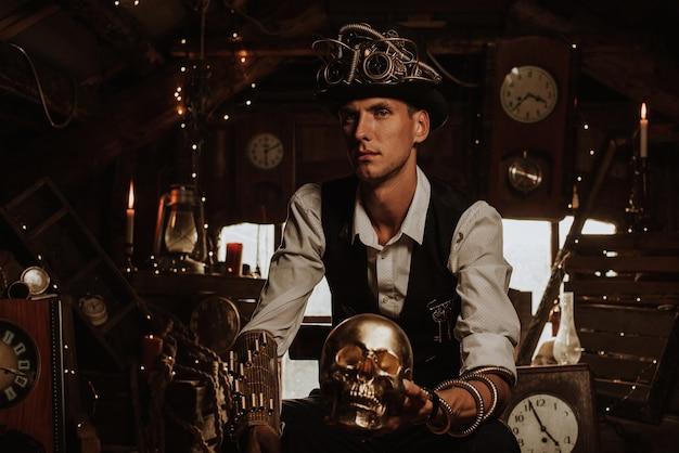 Ingegnere maschio in un abito steampunk in un cappello a cilindro con occhiali e meccanismi