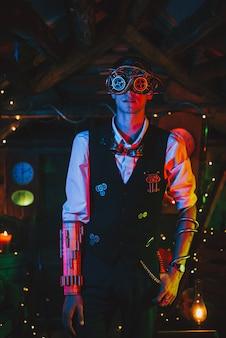 Ingegnere maschio in una tuta steampunk con meccanismi e occhiali in una favolosa atmosfera post-apocalittica