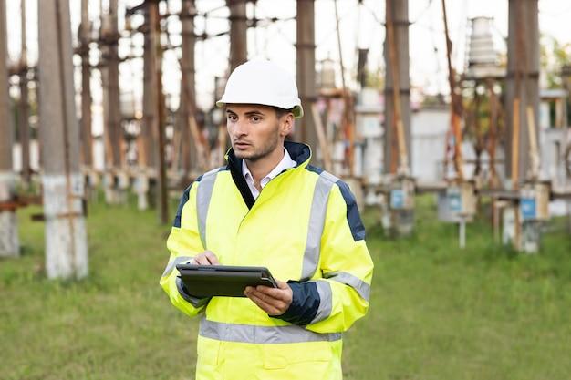 Ingegnere maschio in uniforme e casco in piedi all'aperto e toccando il tablet