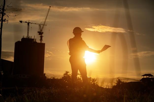Ingegnere maschio che lavora in cantiere all'ora di silhouette sunset