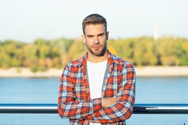 Modello di moda maschile. bellezza maschile. bell'uomo incrociato le mani in camicia a scacchi casual. giovane ragazzo con la barba lunga all'aperto.