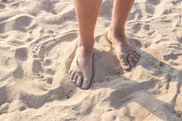 Piedi maschili nella sabbia. cammina lungo la spiaggia sabbiosa del mare in una giornata estiva. viaggi e turismo.