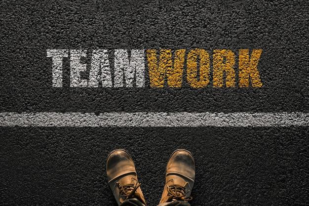 Piedi maschili con scarpe sull'asfalto con un lavoro di squadra di linea e testo, vista dall'alto. scelta del lavoro di squadra e lavoro insieme. vale la pena scegliere il manager, concetto