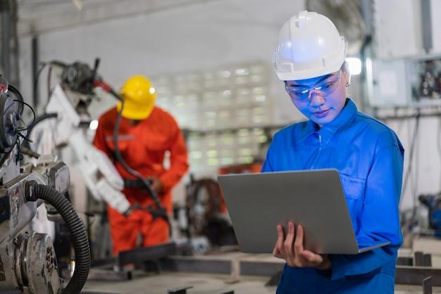 Gli ingegneri dell'automazione maschili e femminili indossano un'uniforme con l'ispezione di sicurezza del casco controllano una saldatrice a braccio robot con un laptop in una fabbrica industriale. concetto di intelligenza artificiale.