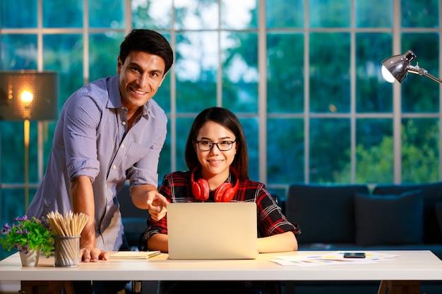 Coppia maschile e femminile che soggiornano insieme in soggiorno al crepuscolo serale e lavorano con un computer portatile, guardando alla telecamera con facce felici. nuova normalità, concetto di lavoro a casa.